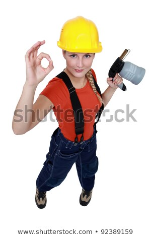 tradeswoman holding a blowtorch and giving the a ok sign stock photo © photography33