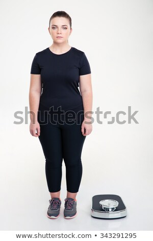 Serious fat woman standing near weighing machine Stock photo © deandrobot