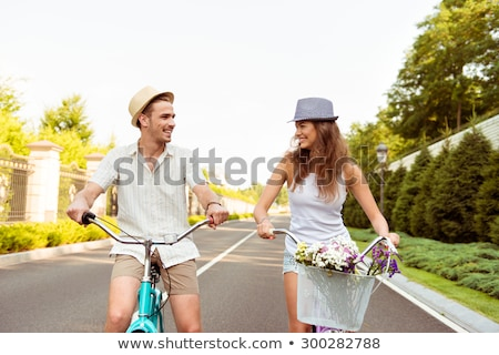lovely young woman in a hat riding a bicycle in a park foto stock © vlad_star