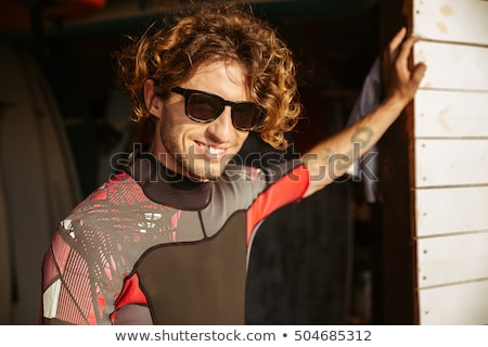 curly man in swimsuit standing at the beach hut stock photo © deandrobot