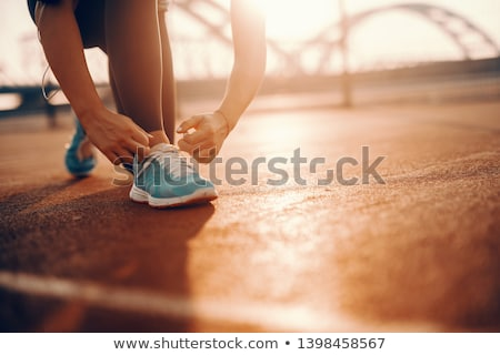Young runner tying shoelaces in park Stock photo © deandrobot