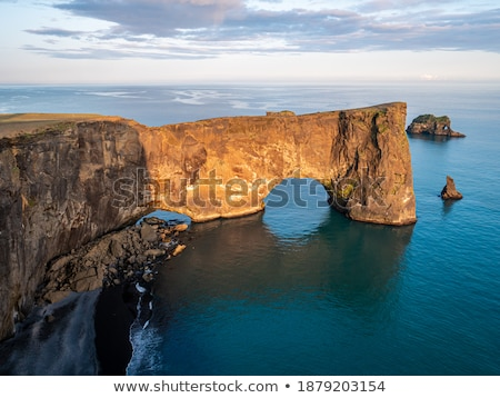 Amazing black arch of lava standing in the sea. Location cape Dy Stock photo © Leonidtit