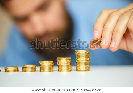 Beared man stacking gold coins into increasing columns Stock photo © vlad_star