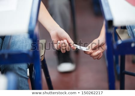 Girl passing a note in class Stock photo © IS2