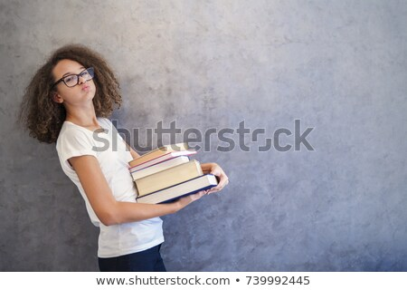 Teenage girl stands by the wall and holds several books Stock photo © boggy