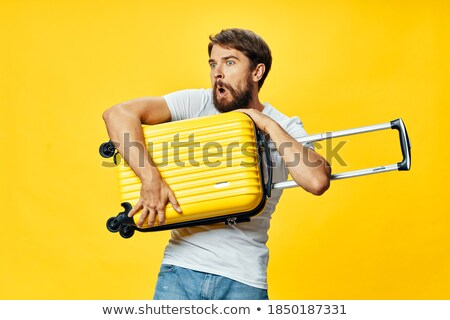 young casual man looking to open his suitcase stock photo © feedough