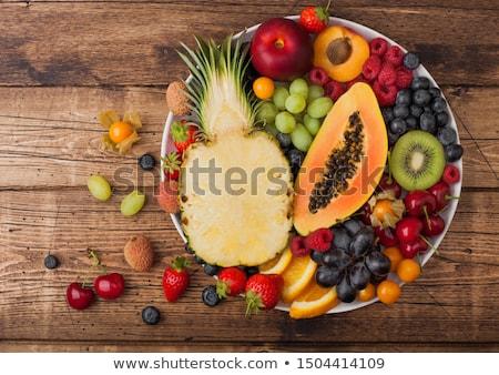 fresh raw organic summer berries and exotic fruits in white plate on dark wooden background pineapp stock photo © denismart