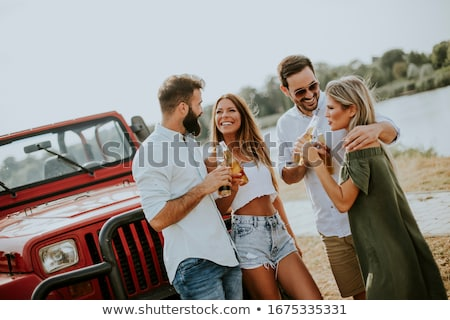 Group of young people  having fun by car outdoor at hot summer d Stock photo © boggy