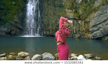 A young woman is standing in a waterfall Stock photo © galitskaya