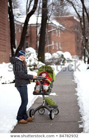young mother with baby in stroller walks street winter stock photo © Lopolo