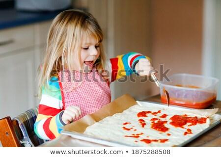 Happy teenagers having fun in the kitchen preparing a pizza Stock photo © ilona75