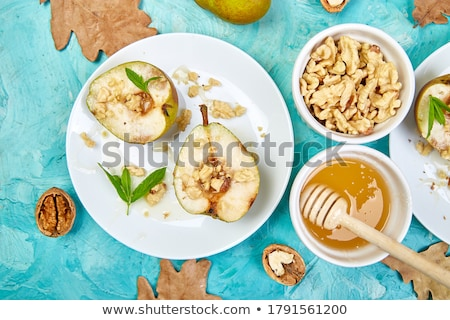 Tasty roast pears with honey and walnuts on blue background table. Stock photo © Illia