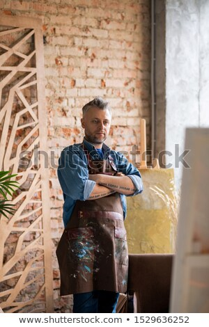 Serious painter with his arms crossed on chest looking at painting on easel Stock photo © pressmaster