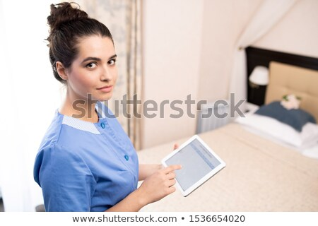 Pretty young chamber maid with touchpad working with electronic documents Stock photo © pressmaster