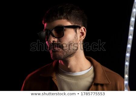 man in sunglasses over ultra violet neon lights Stock photo © dolgachov