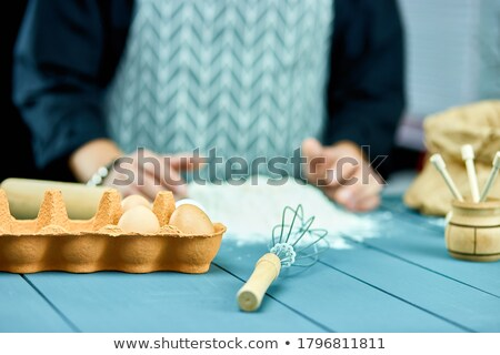 Man forming the dough on a floured surface and kneading it with his hands. Stock photo © Illia