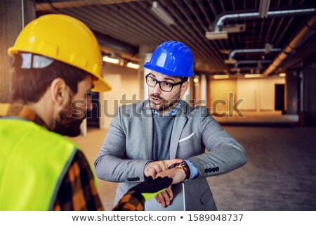 Construction worker and architect discussing work to be done at site Stock photo © Kzenon