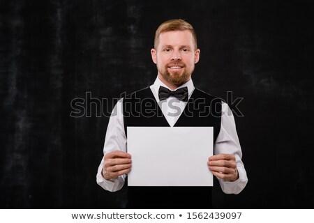 Happy elegant waiter in black waistcoat and bowtie holding blank paper Stock photo © pressmaster