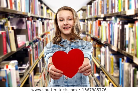 smiling teenage girl with red heart over library Stock photo © dolgachov
