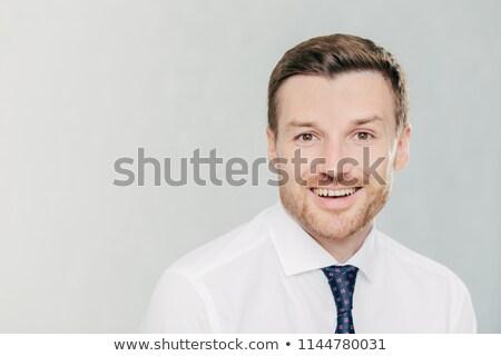 Studio shot of handsome unshaven male entrepreneur with cheerful expression, rejoices raising sales, Stock photo © vkstudio
