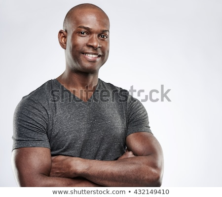 Image of bald african american man standing with arms crossed in Stock photo © deandrobot