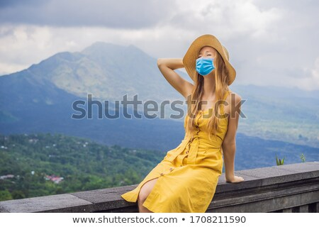 Woman in medical mask traveler looking at Batur volcano. Indonesia Tourists fear the 2019-ncov virus Stock photo © galitskaya
