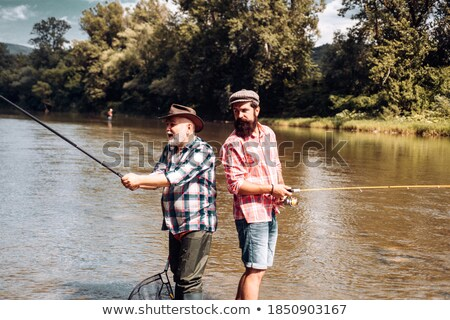 handsome middle-aged fisherman by riverside Stock photo © photography33