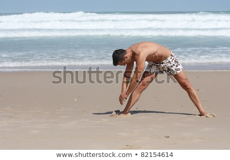 attractive man making stretching movements on the beach stock photo © pedromonteiro