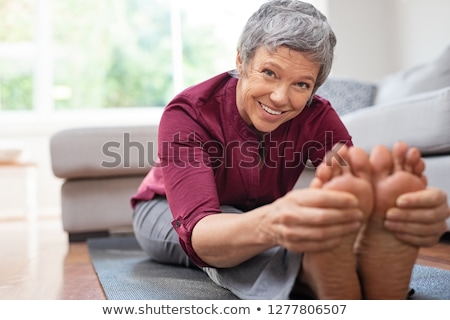 Woman touching her toes on an exercise mat Stock photo © photography33