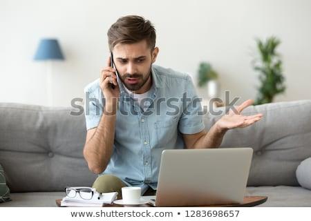 Stock photo: An anxious businessman over the phone.
