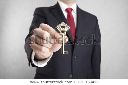 Stock photo: Male hand holding golden key