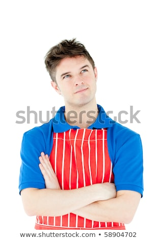 Serious young cook wearing a apron with folded arms against white background Stock photo © wavebreak_media