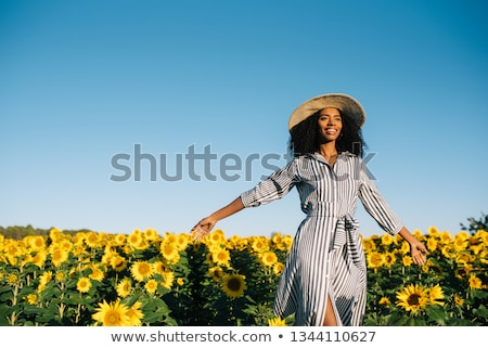 Stock photo: girl in a field of bright sunflowers