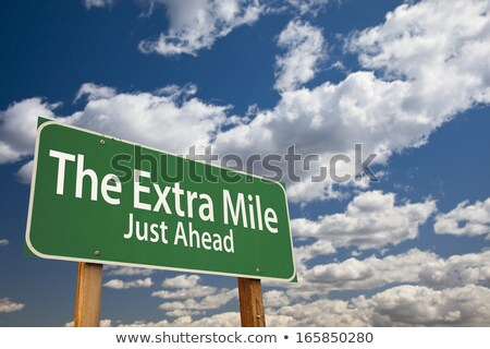 Extra Mile Just Ahead on Green Billboard. Stock photo © tashatuvango
