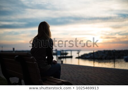 Stock photo: Happy young woman standing watching the sunset over the lake
