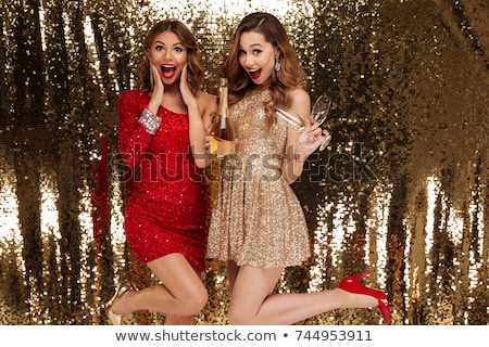 Two champagne glasses and santa hat over bottle Stock photo © karandaev