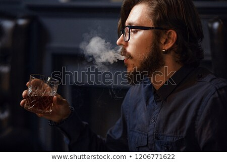 elegant business man holding a cigarette in his left hand stock photo © feedough