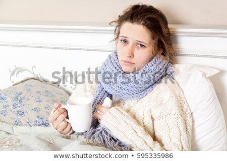Unhappy young woman sitting on the bed and looking on the camera Stock photo © deandrobot