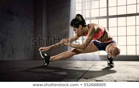 happy sporty woman doing stretching exercises stock photo © deandrobot