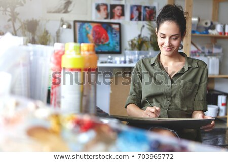 cheerful female painter making sketches in workshop stock photo © deandrobot