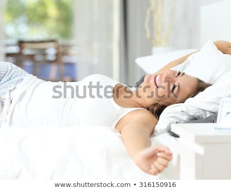 smiling attractive woman in white shirt lying in bed stock photo © deandrobot