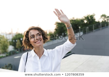 Cheerful Young Lady Waving Her Hand Stock photo © robuart