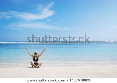 Woman sitting cross legged on beach Stock photo © IS2