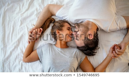 Young man and woman flirting and hugging in bed Stock photo © deandrobot