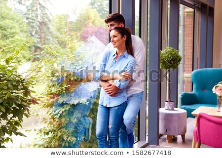 lovely young couple standing by the window stock photo © boggy