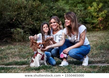 Fiatal nő térdel kutya mosolyog díszállat Magyarország Stock fotó © IS2