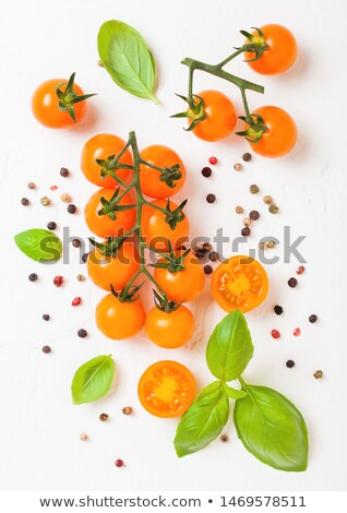 Organic Cherry Orange Rapture Tomatoes on the Vine with basil and pepper on white kitchen background Stock photo © DenisMArt