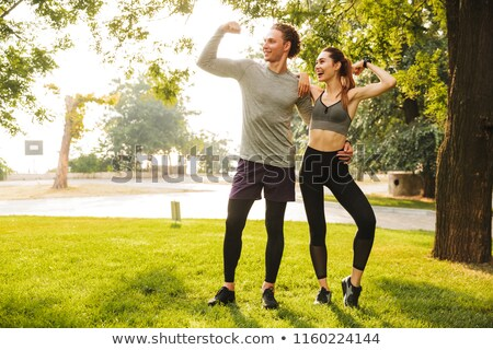 Image of beautiful sporty couple man and woman 20s in tracksuits Stock photo © deandrobot