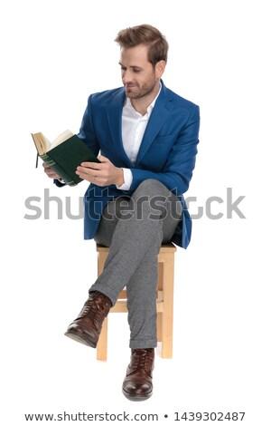 Atraente homem leitura livro sessão as pernas cruzadas Foto stock © feedough