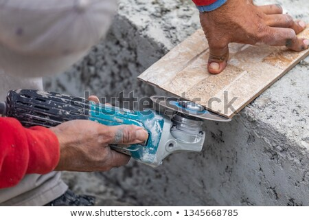 Worker Grinding Corner Tile for Fitting Stock photo © feverpitch